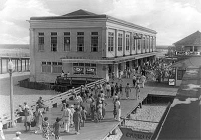 people walking down the boardwalk in 1930