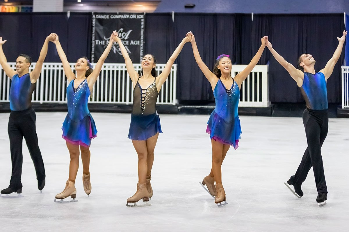 group of figure skaters on ice rink posing with arms up in finale pose
