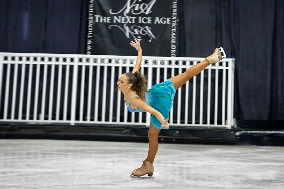 female figure skater performs in ice rink