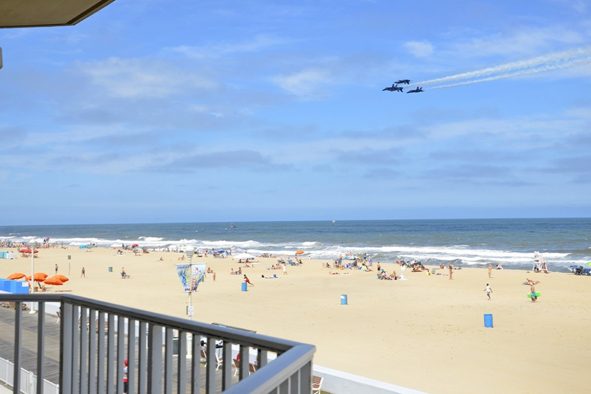 balcony view of beach, mostly blue sky, and Blue Angels jets flyby